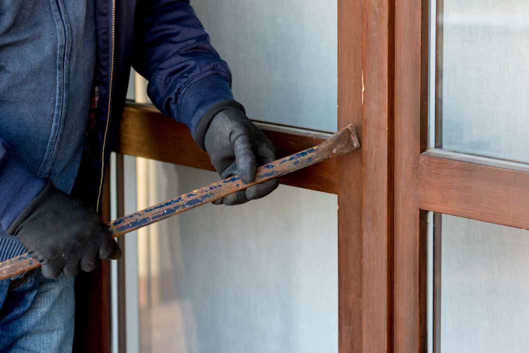 milan italy november a thief trying to burden a window door with the crowbar to enter the t WnXZY